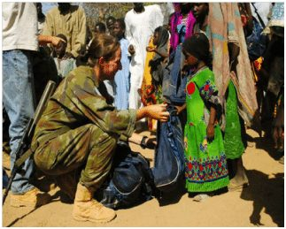 Lieutenant Karen O'Sullivan presenting the locals of Ridjil Doud, in Chad with the Friends of St. Patrick Aid. (Photograph courtesy of the Defence Forces)